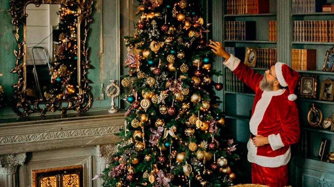 Santa Claus face à un arbre de Noel.